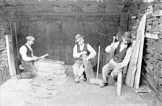 A team of quarrymen splitting slates