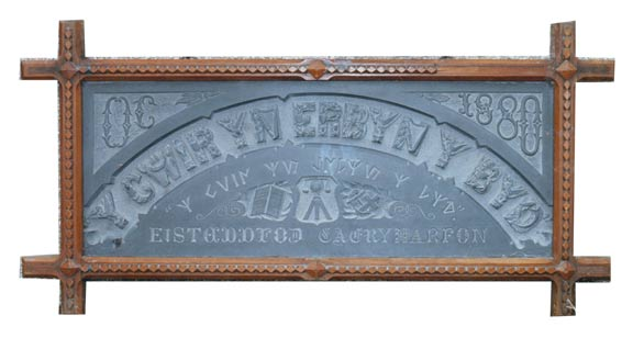 A slate carving from 1880 with the motto `Y Gwir yn erbyn y Byd' (The Truth against the World'.)